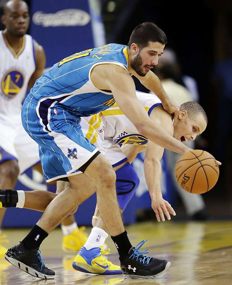 New Orleans Hornets' Greivis Vasquez (21) fights for a loose ball against Golden State Warriors' Stephen Curry (30) during the first half of an NBA basketball game in Oakland, Calif., Tuesday, Dec. 18, 2012. (AP Photo/Marcio Jose Sanchez) Photo: Marcio Jose Sanchez, Associated Press