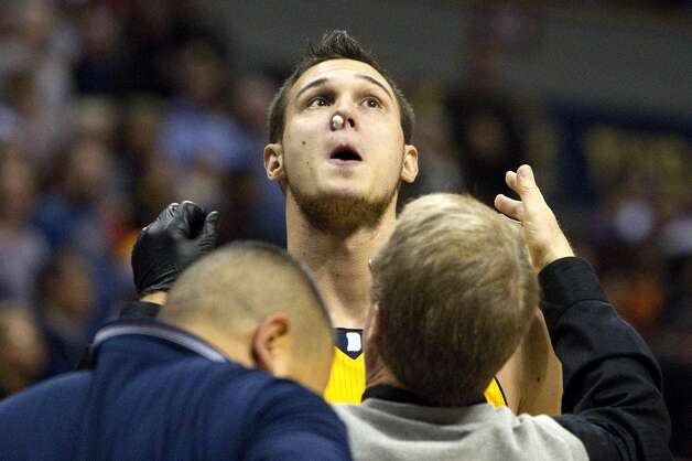 Denver Nuggets forward Danilo Gallinari is treated for a bloody nose during the first quarter of an NBA basketball game against the San Antonio Spurs on Tuesday, Dec. 18, 2012, in Denver. (Barry Gutierrez / Associated Press)