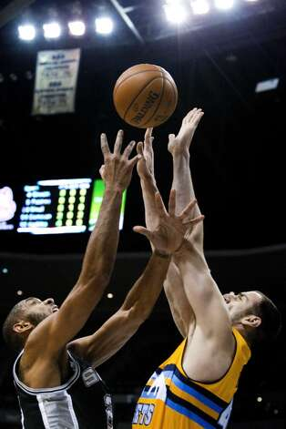 San Antonio Spurs' Tim Duncan, left, and Denver Nuggets' Kosta Koufos, right, compete for a rebound during the first quarter of an NBA basketball game Tuesday, Dec. 18, 2012, in Denver. (Barry Gutierrez / Associated Press)
