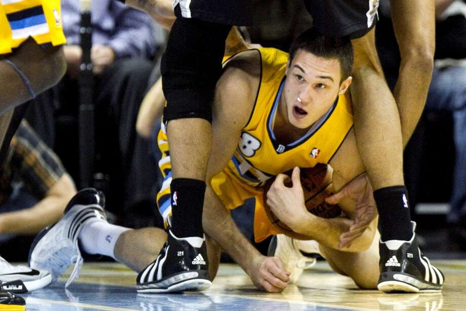 Denver Nuggets' Danilo Gallinari (8) grabs a loose ball while crawling between the legs of San Antonio Spurs' Tim Duncan during the first quarter of an NBA basketball game Tuesday, Dec. 18, 2012 in Denver. (Barry Gutierrez / Associated Press)