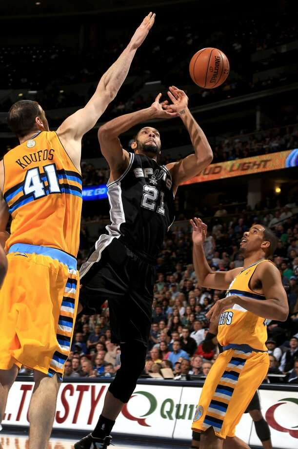 Tim Duncan #21 of the San Antonio Spurs looses control of the ball against Kosta Koufos #41 and Andre Miller #24 of the Denver Nuggets at the Pepsi Center on December 18, 2012 in Denver, Colorado. The Nuggets defeated the Spurs 112-106. (Doug Pensinger / Getty Images)