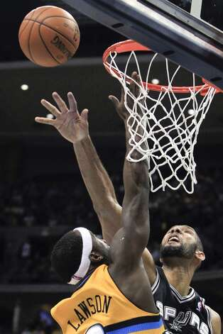 San Antonio Spurs' Tim Duncan, right, blocks a shot by Denver Nuggets' Ty Lawson during the third quarter of an NBA basketball game Tuesday, Dec. 18, 2012, in Denver. The Nuggets won 112-106. (Barry Gutierrez / Associated Press)