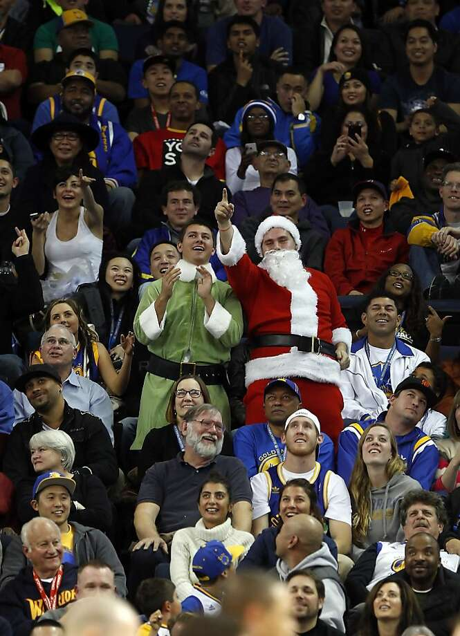 Two fans dressed as Santa Claus and an elf danced during one of the timeouts during the Warriors game. The Golden State Warriors played the New Orleans Hornets at OracleArena in Oakland, Calif., on Tuesday, December 18, 2012, defeating the Hornets 103-96 Photo: Carlos Avila Gonzalez, The Chronicle