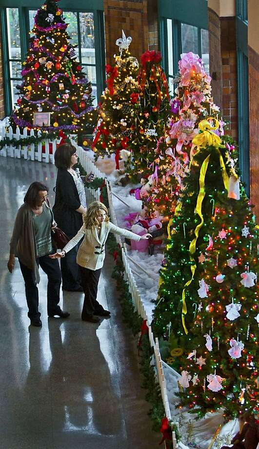 Barbara Nugent, left, of Kansas City North, tours the Hall of Trees with her granddaughter, Ema Arasmith,7, and her daughter Amy Arasmith, background, both of Harrisburg, Pa., on Tuesday, Dec. 18, 2012 in the Hall of Waters Cultural Museum in downtown Excelsior Springs, Mo. The trees, decorated by various churches, businesses and non-profits, are on display until Jan. 1, 2013. Admission is free and the hours are Monday - Saturday 9 a.m. to 5 p.m. and on Sundays from 11 a.m. to 4 p.m. Photo: Allison Long, Associated Press
