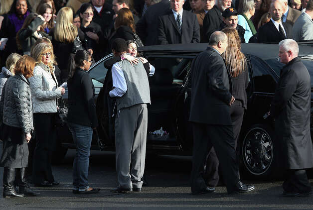 NEWTOWN, CT - DECEMBER 18:  Mourners embrace after a funeral for Jessica Rekos, 6, at the St. Rose of Lima Catholic church on December 18, 2012 in Newtown, Connecticut. Funeral services were held at the church for both Jessica Rekos and James Mattioli, 6, Tuesday, four days after 20 children and six adults were killed at Sandy Hook Elementary School. Photo: John Moore, Getty Images / 2012 Getty Images