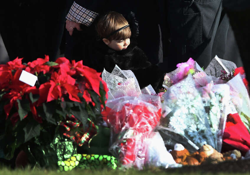 NEWTOWN, CT - DECEMBER 18:  A child stands next to a makeshift memorial for Jessica Rekos, 6, follow