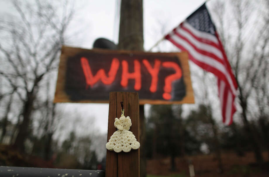 NEWTOWN, CT - DECEMBER 18:  A knitted angel and a sign hang near a cemetery on December 18, 2012 in Newtown, Connecticut. Funeral services were held in Newtown Tuesday for Jessica Rekos, 6, and James Mattioli, 6, four days after 20 children and six adults were killed at Sandy Hook Elementary School. Photo: John Moore, Getty Images / 2012 Getty Images