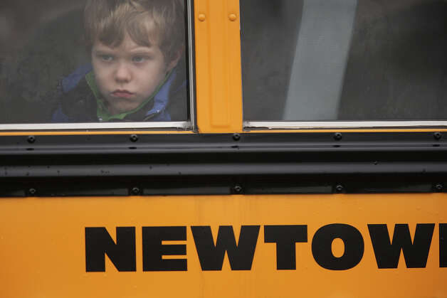 NEWTOWN, CT - DECEMBER 18:  A child gazes from a school bus as it passes by the St. Rose of Lima Catholic church while mourners gathered for a funeral service for shooting victim Jessica Rekos, 6,  on December 18, 2012 in Newtown, Connecticut. Four days after 20 children and six adults were killed at Sandy Hook Elementary School, most students in Newtown returned to school. Children at Sandy Hook Elementary will attend a school in a neighboring town until authorities decide whether or not to reopen their school. Photo: John Moore, Getty Images / 2012 Getty Images