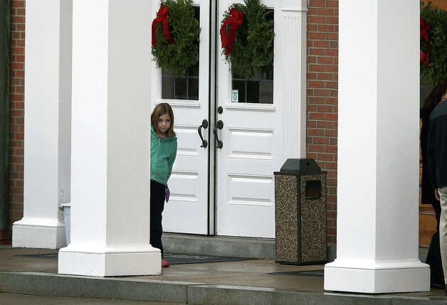 NEWTOWN, CT - DECEMBER 18:  A child stands at the entrance of the St. Rose of Lima Catholic church ahead of the funeral of James Mattioli, 6, on December 18, 2012 in Newtown, Connecticut. Funeral services were held at the church for both James Mattioli and Jessica Rekos, 6, Tuesday, four days after 20 children and six adults were killed at Sandy Hook Elementary School. Photo: John Moore, Getty Images / 2012 Getty Images