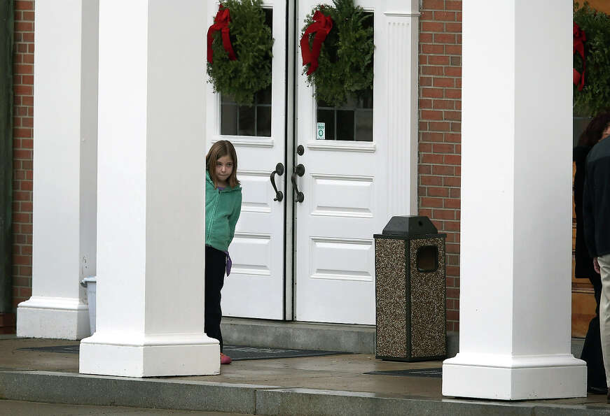 NEWTOWN, CT - DECEMBER 18:  A child stands at the entrance of the St. Rose of Lima Catholic church a