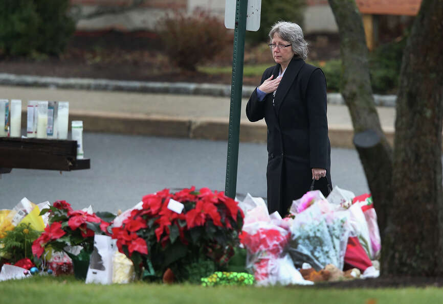 NEWTOWN, CT - DECEMBER 18:  A mourner pays respects at a makeshift memorial following a funeral for