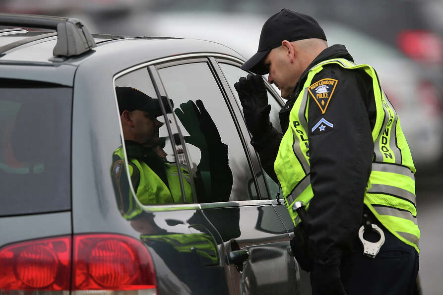 NEWTOWN, CT - DECEMBER 18:  Police check a car arrving for the funeral of shooting victim James Matt