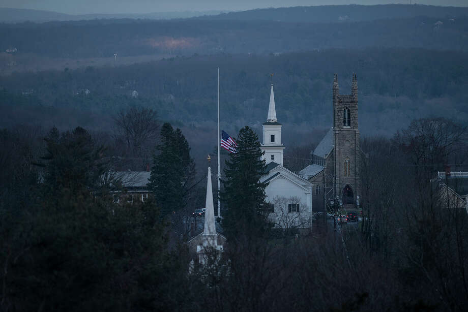 A view of the Newtown Meetinghouse and Trinity Episcopal Church as Main Street's flag flies at half-staff on December 18, 2012 in Newtown, Connecticut. Newtown continues to mourn the loss of 20 students and 6 adults from last Friday's shooting as Sandy Hook Elementary School with a second day of funerals.  AFP PHOTO/Brendan SMIALOWSKI Photo: BRENDAN SMIALOWSKI, AFP/Getty Images / 2012 AFP