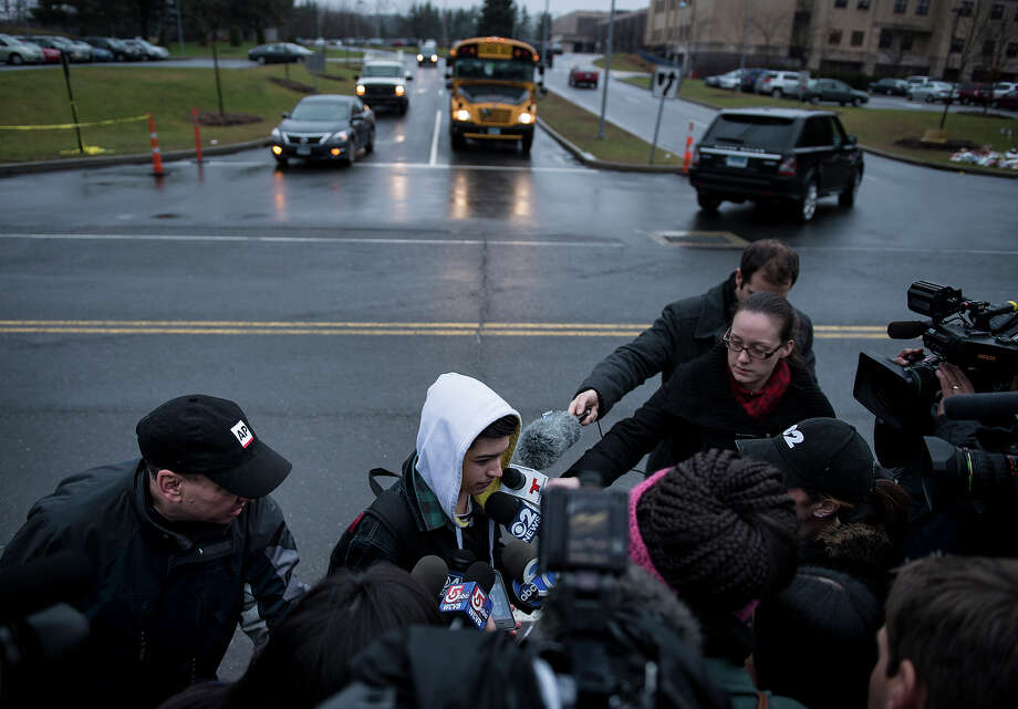 Reporters interview Newtown High School sophomore Tate Schwab while he walks to school on December 18, 2012 in Newtown, Connecticut. Students in Newtown, excluding Sandy Hook Elementary School, return to school for the first time since last Friday's shooting at Sandy Hook which took the live of 20 students and 6 adults.      AFP PHOTO/Brendan SMIALOWSKI Photo: BRENDAN SMIALOWSKI, AFP/Getty Images / 2012 AFP