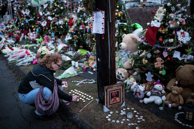 A woman lights candles at a makeshift memorial near the entrance to the grounds of Sandy Hook Elementary School on December 18, 2012 in Newtown, Connecticut. Students in Newtown, excluding Sandy Hook Elementary School, return to school for the first time since last Friday's shooting at Sandy Hook which took the live of 20 students and 6 adults.  AFP PHOTO/Brendan SMIALOWSKI Photo: BRENDAN SMIALOWSKI, AFP/Getty Images / 2012 AFP
