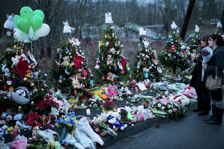 Two women visit a makeshift memorial near the entrance to the grounds of Sandy Hook Elementary School on December 18, 2012 in Newtown, Connecticut. Students in Newtown, excluding Sandy Hook Elementary School, return to school for the first time since last Friday's shooting at Sandy Hook which took the live of 20 students and 6 adults.  AFP PHOTO/Brendan SMIALOWSKI Photo: BRENDAN SMIALOWSKI, AFP/Getty Images / 2012 AFP