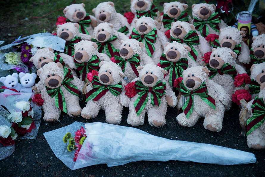Stuffed animals and flowers are seen at a makeshift memorial near the entrance to the grounds of San