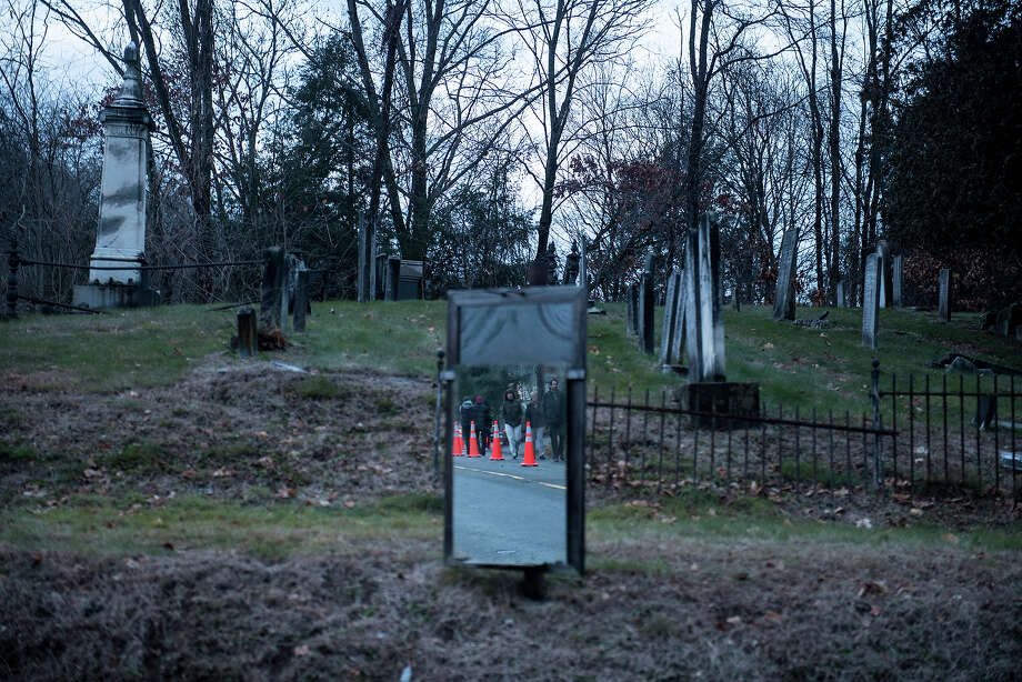 People are reflected in a mirror in a graveyard while they walk up a closed road to a makeshift memorial near the entrance to the grounds of Sandy Hook Elementary School on December 18, 2012 in Newtown, Connecticut. Students in Newtown, excluding Sandy Hook Elementary School, returned to school for the first time since last Friday's shooting at Sandy Hook which took the live of 20 students and 6 adults.  AFP PHOTO/Brendan SMIALOWSKI Photo: BRENDAN SMIALOWSKI, AFP/Getty Images / 2012 AFP