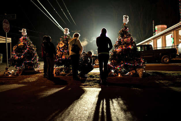People visit a makeshift memorial at Sandy Hook Fire Department near the entrance to the grounds of Sandy Hook Elementary School on December 18, 2012 in Newtown, Connecticut. Students in Newtown, excluding Sandy Hook Elementary School, returned to school for the first time since last Friday's shooting at Sandy Hook which took the live of 20 students and 6 adults.  AFP PHOTO/Brendan SMIALOWSKI Photo: BRENDAN SMIALOWSKI, AFP/Getty Images / 2012 AFP