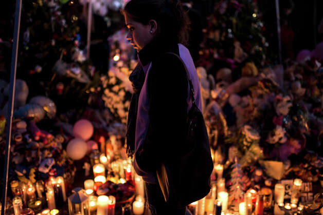 A woman visits a makeshift memorial near the center of Sandy Hook on December 18, 2012 in Newtown, Connecticut. Students in Newtown, excluding Sandy Hook Elementary School, returned to school for the first time since last Friday's shooting at Sandy Hook which took the live of 20 students and 6 adults.  AFP PHOTO/Brendan SMIALOWSKI Photo: BRENDAN SMIALOWSKI, AFP/Getty Images / 2012 AFP