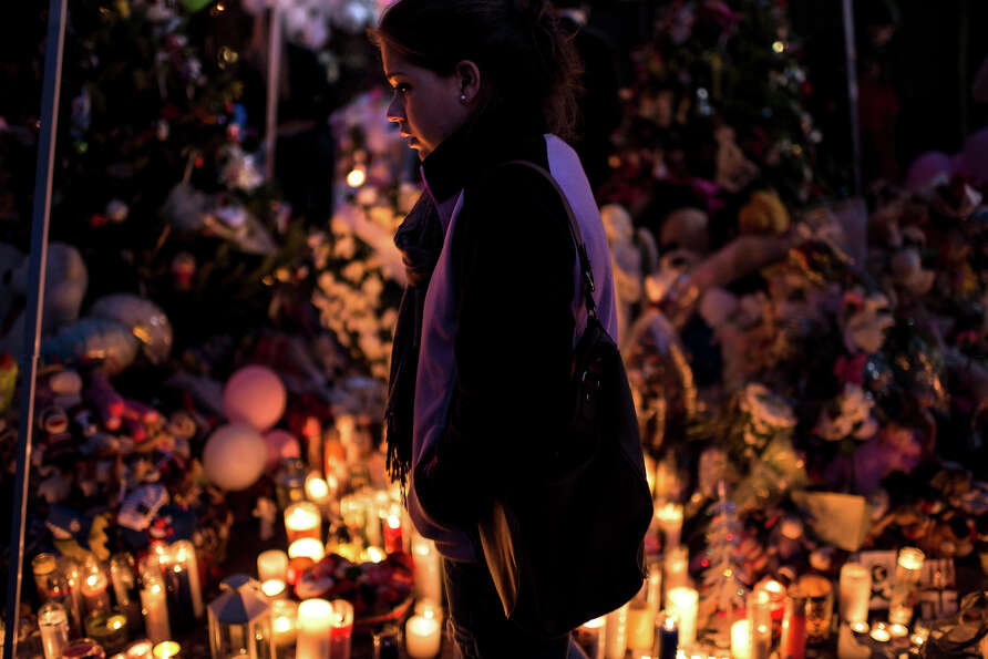 A woman visits a makeshift memorial near the center of Sandy Hook on December 18, 2012 in Newtown, C