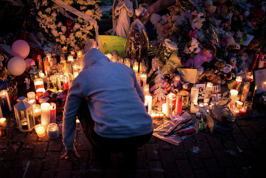 A person visits a makeshift memorial on December 18, 2012 in Newtown, Connecticut. Students in Newtown, excluding Sandy Hook Elementary School, returned to school for the first time since last Friday's shooting at Sandy Hook which took the live of 20 students and 6 adults.  AFP PHOTO/Brendan SMIALOWSKI Photo: BRENDAN SMIALOWSKI, AFP/Getty Images / 2012 AFP
