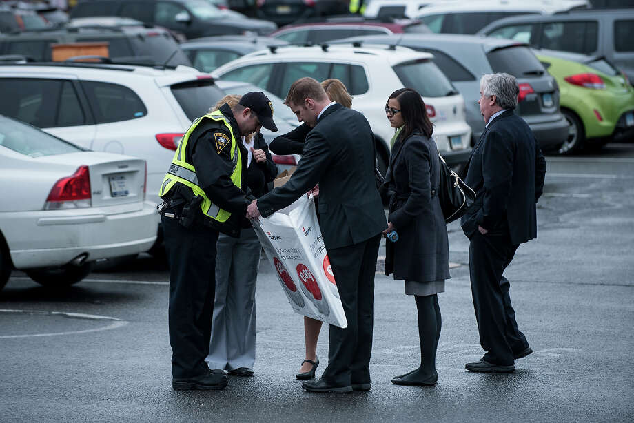 A police officer looks through a bag with a sign as people arrive for a funeral Mass at St. Rose of Lima Roman Catholic Church on December 18, 2012 in Newtown, Connecticut, following last Friday's shooting at Sandy Hook Elementary School which took the lives of 20 students and 6 adults.  AFP PHOTO/Brendan SMIALOWSKI Photo: BRENDAN SMIALOWSKI, AFP/Getty Images / 2012 AFP