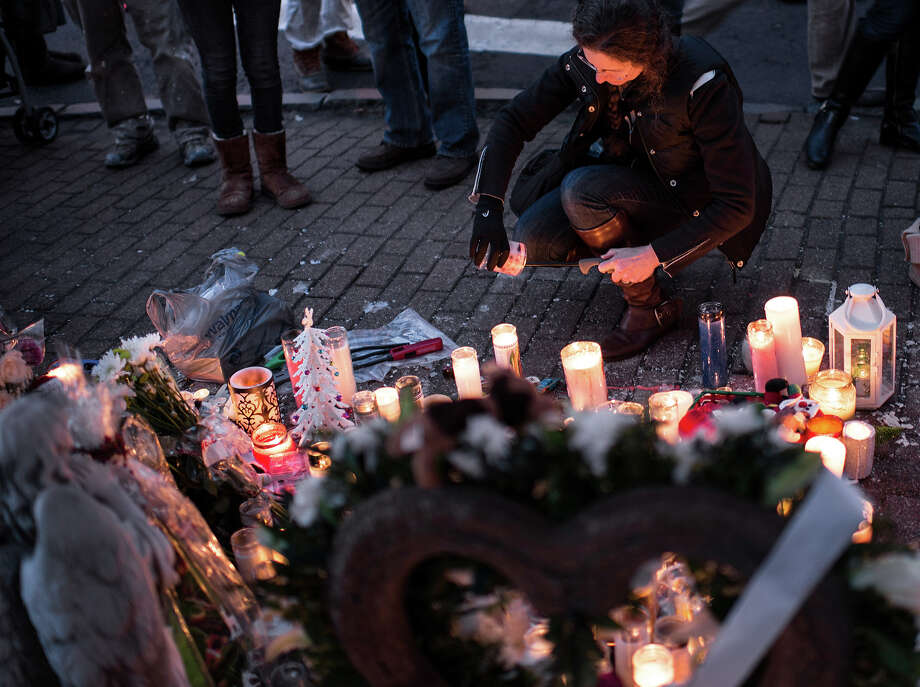 A woman lights a candle at a makeshift memorial on December 18, 2012 in Newtown, Connecticut. Students in Newtown, excluding Sandy Hook Elementary School, returned to school for the first time since last Friday's shooting at Sandy Hook which took the live of 20 students and 6 adults.  AFP PHOTO/Brendan SMIALOWSKI Photo: BRENDAN SMIALOWSKI, AFP/Getty Images / 2012 AFP