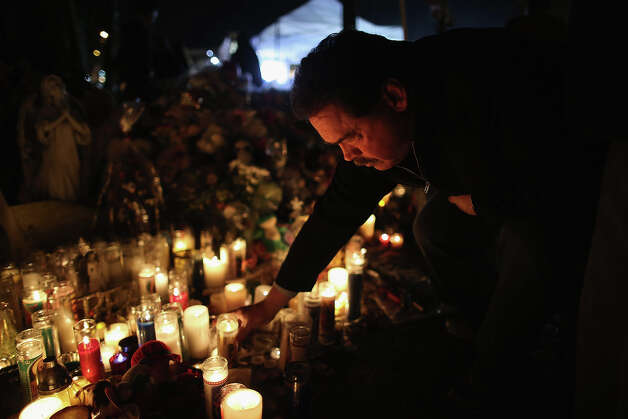 NEWTOWN, CT - DECEMBER 18:  A mourner places a candle while visiting a makeshift memorial for shooting victims on December 18, 2012 in Newtown, Connecticut. Funeral services were held in Newtown Tuesday for Jessica Rekos and James Mattioli, both age six, four days after 20 children and six adults were killed at Sandy Hook Elementary School. Photo: John Moore, Getty Images / 2012 Getty Images