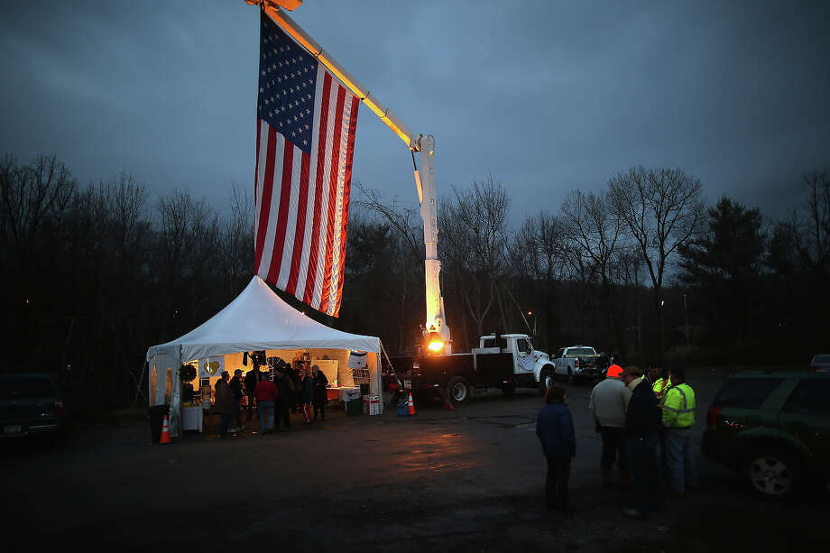 NEWTOWN, CT - DECEMBER 18:  A flag hangs over a memorial for shooting victims on December 18, 2012 in Newtown, Connecticut. Funeral services were held in Newtown Tuesday for Jessica Rekos and James Mattioli, both age six, four days after 20 children and six adults were killed at Sandy Hook Elementary School. Photo: John Moore, Getty Images / 2012 Getty Images