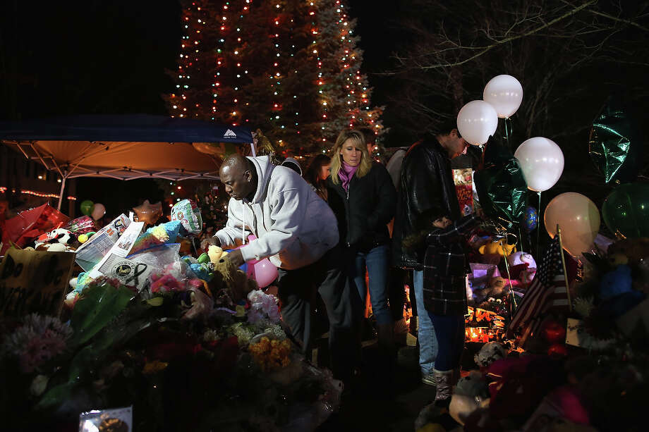 NEWTOWN, CT - DECEMBER 18:  A mourner places a stuffed animal while visiting a makeshift memorial for shooting victims on December 18, 2012 in Newtown, Connecticut. Funeral services were held in Newtown Tuesday for Jessica Rekos and James Mattioli, both age six, four days after 20 children and six adults were killed at Sandy Hook Elementary School. Photo: John Moore, Getty Images / 2012 Getty Images