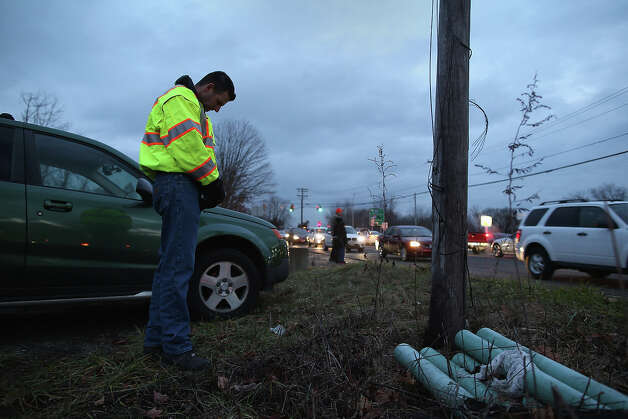 NEWTOWN, CT - DECEMBER 18:  Volunteer chaplain Jesse Hardy pays respects as a group of mourners pass by on December 18, 2012 in Newtown, Connecticut. Wakes were held for numerous victims and funeral services for Jessica Rekos and James Mattioli, both age six, four days after 20 children and six adults were killed at Sandy Hook Elementary School. Photo: John Moore, Getty Images / 2012 Getty Images