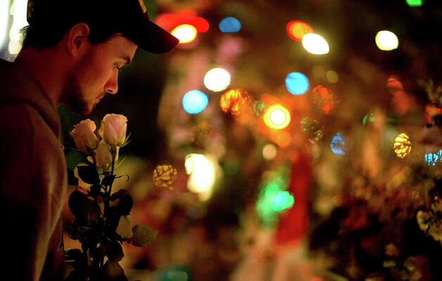 A Newtown resident who identified himself only as Andrew, holds roses as he visits a memorial for the Sandy Hook Elementary School shooting victims, Tuesday, Dec. 18, 2012, in Newtown, Conn. Photo: AP