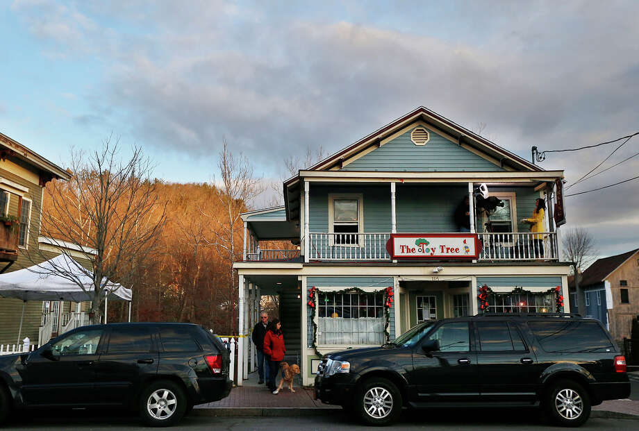 A couple, bottom left, walks with a dog while a television news crew, top right, works on the balcony of a store in the Sandy Hook village of Newtown, Conn., as media presence is seen in the aftermath of the elementary school shooting that shocked the small, quiet town, Wednesday, Dec. 19, 2012. News about the shooting spread quickly across the world, prompting media outlets to set camp in the small town. The gunman, Adam Lanza, walked into Sandy Hook Elementary School in Newtown, Conn., Dec. 14, and opened fire, killing 26 people, including 20 children, before killing himself. Photo: AP
