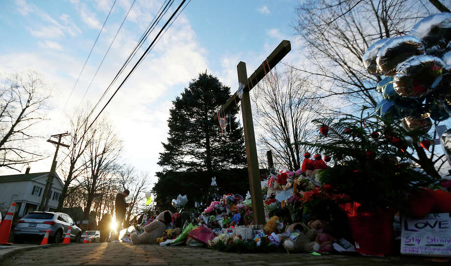 A man visiting from Michigan takes photos of a makeshift memorial near the town Christmas tree in the Sandy Hook village of Newtown, Conn., Wednesday, Dec. 19, 2012. The memorial, which was put up in the aftermath of the elementary school shooting that shocked the small town, is increasing in size as the days go on. More funerals are scheduled for Wednesday, as the town continues to mourn its victims. The gunman, Adam Lanza, walked into Sandy Hook Elementary School in Newtown, Conn., Dec. 14, and opened fire, killing 26 people, including 20 children, before killing himself. Photo: AP