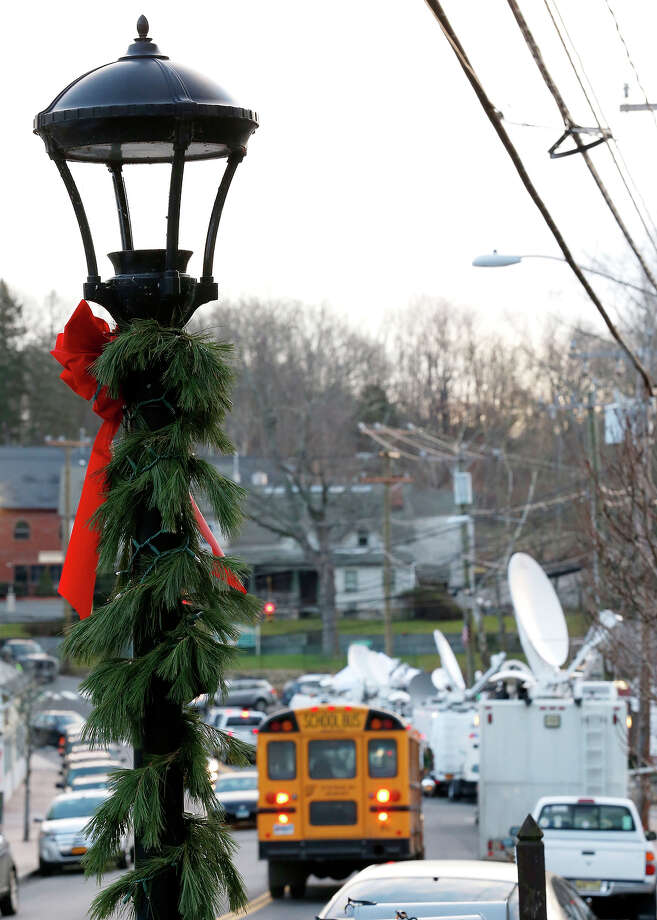 A street lamp decorated for the holidays stands as a school bus rides through a main road in the Sandy Hook village of Newtown, Conn., as the strong media presence is seen in the aftermath of the elementary school shooting that shocked the small, quiet town, Wednesday, Dec. 19, 2012. News about the shooting spread quickly across the world, prompting media outlets to set camp in the small town. The gunman, Adam Lanza, walked into Sandy Hook Elementary School in Newtown, Conn., Dec. 14, and opened fire, killing 26 people, including 20 children, before killing himself. Photo: AP