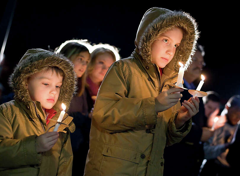 Landon Coley, 6, left, with brother Ethan, 9, hold lit candles during the reading of names on Tuesda