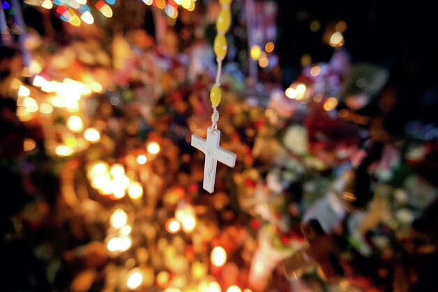 A cross hangs above a sidewalk memorial in honor of the Sandy Hook Elementary School shooting victims, Tuesday, Dec. 18, 2012, in Newtown, Conn. Photo: AP