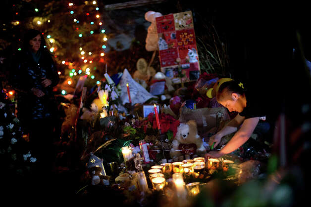 Glenn Mackbach, 17, of Sudbury, Conn., lights a candle that went out at a memorial in honor of the Sandy Hook Elementary School shooting victims, Tuesday, Dec. 18, 2012, in Newtown, Conn. Mackbach and his friends have been coming down when they get out of school and work to relight candles at the memorials. Photo: AP