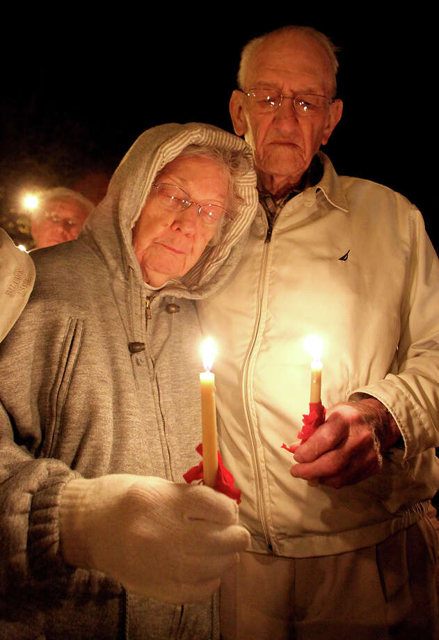 From left, Frankie and George Martin hold candles as prayers are said  for the victims and family members affected by the Newtown, Conn. school shooting, Tuesday, Dec. 18, 2012 on the court square in Shelby, N.C. Photo: AP