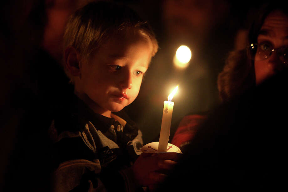 Caleb Saunders, 2, holds a candle close as prayer is said for the 26 lives lost in Newtown, Conn. at a vigil on the court square in uptown Shelby, N.C. on Tuesday, Dec. 18, 2012. Photo: AP