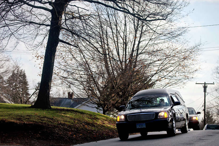 A hearse leads a funeral procession to St. Rose of Lima Parish Cemetery for the burial of 6-year-old Sandy Hook Elementary School shooting victim Jessica Rekos, Tuesday, Dec. 18, 2012, in Newtown, Conn. Photo: AP