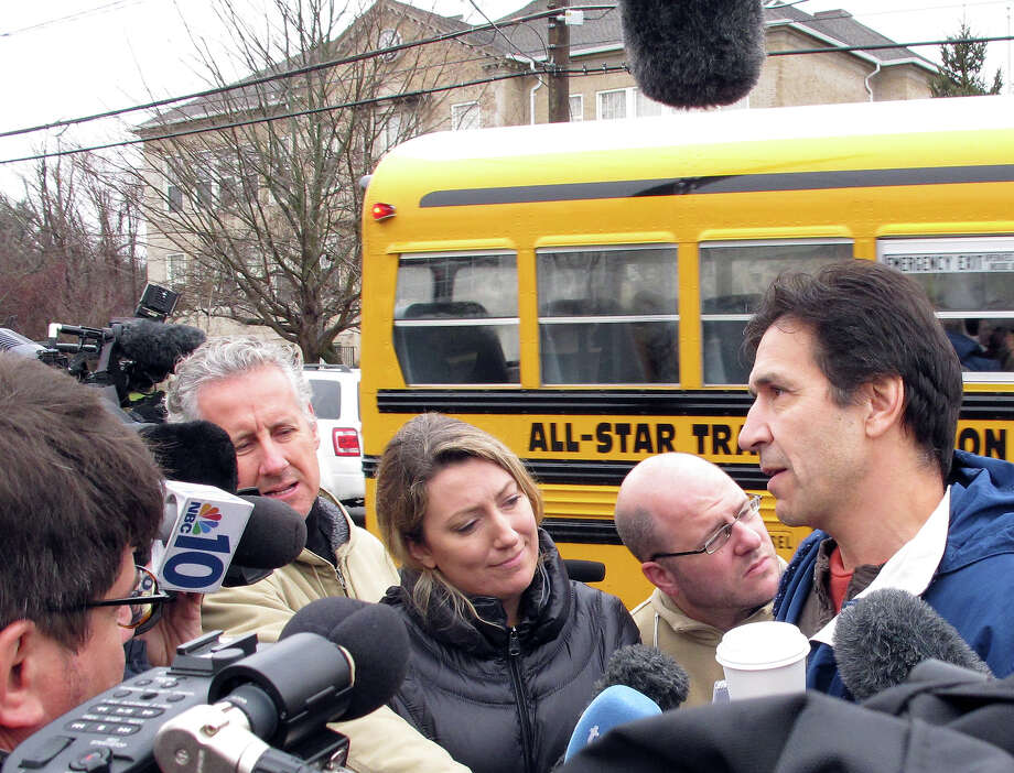 """Peter Muckell, right, talks with reporters after dropping off his daughter, Shannon, 8, at Hawley Elementary School on Tuesday, Dec. 18, 2012. Muckell said last week's mass school shooting at Sandy Hook Elementary couldn't have been prevented, and he feels the schools are as safe as they can be. """"Is there ever a right day? I mean, you just do it, you know, just get them back to school,"""" said Peter Muckell as he took 8-year-old daughter Shannon, a third-grader, to Hawley Elementary. Photo: AP"""