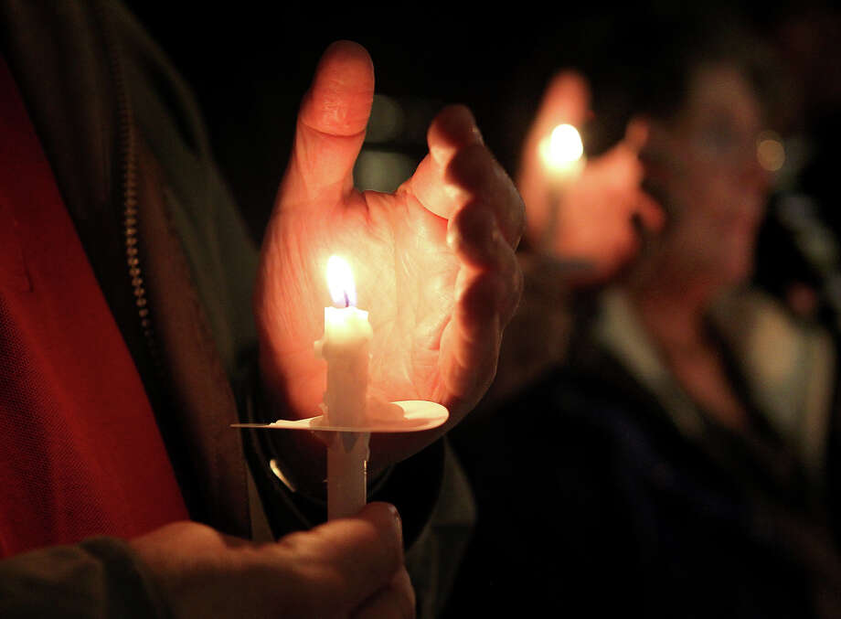 An attendee protects his candle flame as names of victims are read aloud during a candlelight Vigil for Peace for the victims of the Newtown, Conn. massacre on Tuesday, Dec. 18, 2012, on the steps of the Main Public Library in downtown St. Louis, Mo. Religious leaders from a variety of faiths gathered with about 200 others at Christ Church Cathedral Episcopal Church for an interfaith ceremony, which was followed by the reading of names. Photo: AP