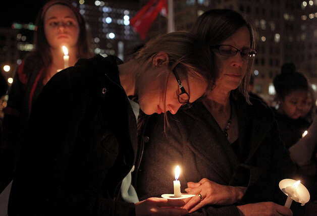 Julianna Nikodym, 15, (center) and her mother Vicki Swyers (right) listen to the names of shooting victims read aloud during a candlelight Vigil for Peace for the victims of the Newtown, Conn. massacre on Tuesday, Dec. 18, 2012, on the steps of the Main Public Library in downtown St. Louis, Mo. Religious leaders from a variety of faiths gathered with about 200 others at Christ Church Cathedral  Episcopal Church for an interfaith ceremony, which was followed by the reading of names. Photo: AP