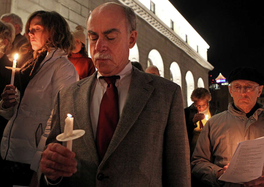 Carly Woodridge (left) and Tom Edelmann listen to the names of shooting victims read aloud during a candlelight Vigil for Peace for the victims of the Newtown, Conn. massacre on Tuesday, Dec. 18, 2012, on the steps of the Main Public Library in downtown St. Louis, Mo. Religious leaders from a variety of faiths gathered with about 200 others at Christ Church Cathedral Episcopal Church for an interfaith ceremony, which was followed by the reading of names. Photo: AP