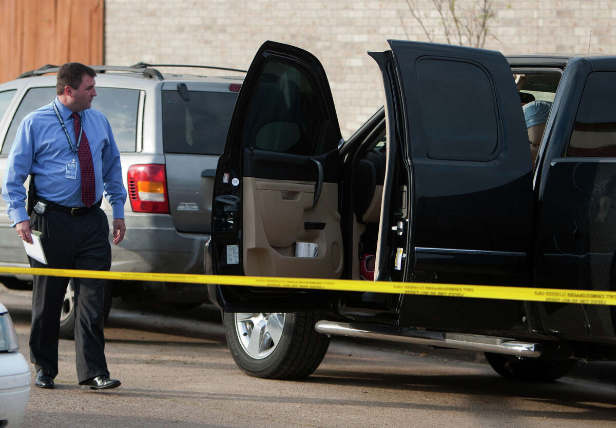Police investigate a scene after a man was found dead in his truck on Lost Forest Drive near Pinemont Drive, Wednesday, Dec. 19, 2012, in Houston.