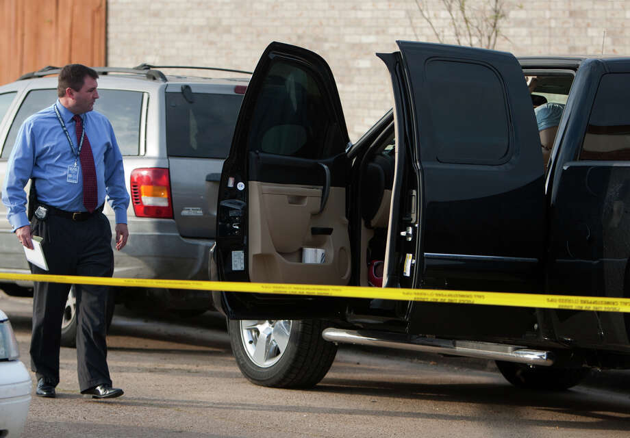 Police investigate a scene after a man was found dead in his truck on Lost Forest Drive near Pinemont Drive, Wednesday, Dec. 19, 2012, in Houston. Photo: Cody Duty, Houston Chronicle / © 2012 Houston Chronicle