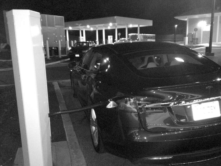 Ken Edwards' car, a Tesla Model S all-electric sedan, gets some juice at a supercharging station in Milford. Photo: Contributed Photo