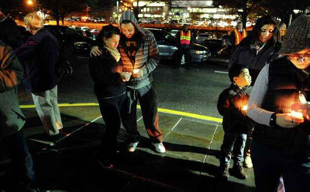 Emily LaMotta and John Perez, center, take part in a candlelight vigil held to remember the Newtown massacre victims at Norwalk Community College in Norwalk, Conn. on Tuesday December 18, 2012. Photo: Christian Abraham / Connecticut Post